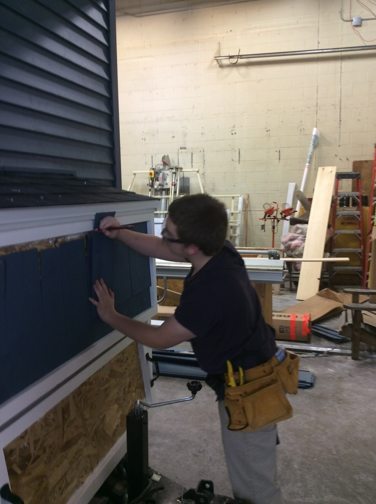 A student installs blue cedar shakes on a propane box.